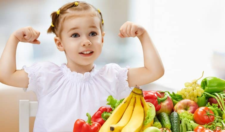 young child flexing muscles next to pile of fruit and vegetables