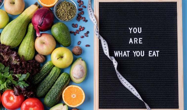fruits and vegetables next to sign you are what you eat