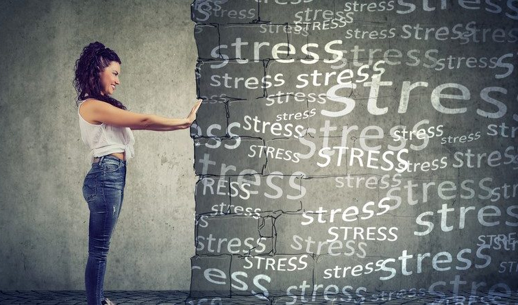 """woman pushing against wall with """"stress"""" written on it"""